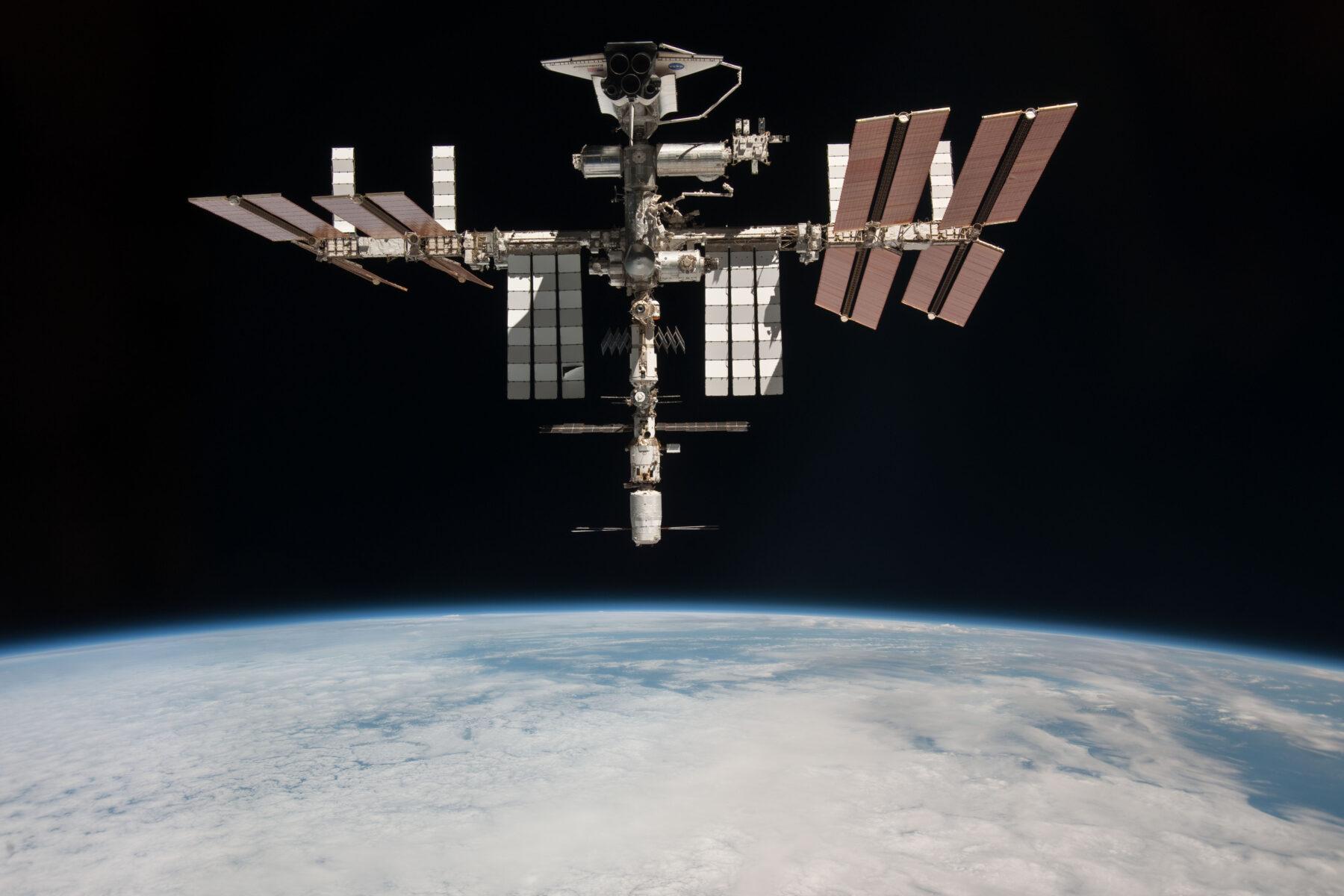 hoto de la station spatiale internationale prise en mai 2011 par l'astronaute italien Paolo Nespoli depuis une capsule russe Soyouz en route vers la Terre. En haut de l'image on aperçoit Endeavour pendant l'avant-dernière mission d'une navette spatiale : STS-134. Crédit : NASA